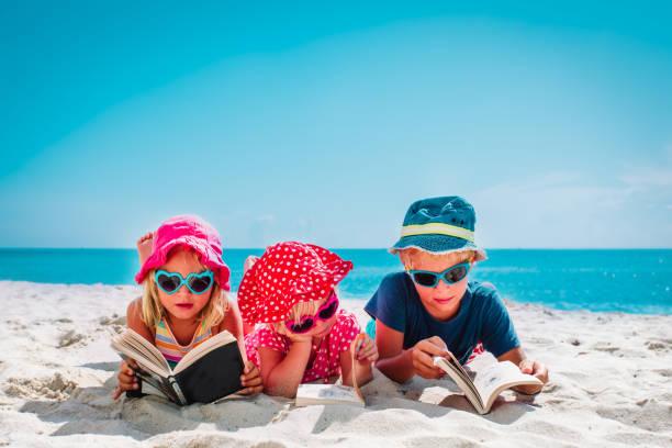 Niños leyendo en la playa